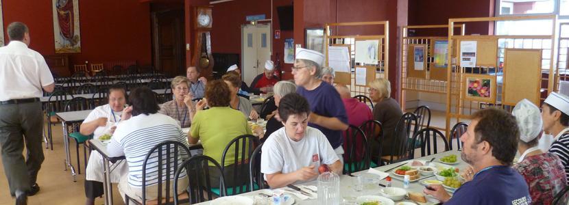 Des bénévoles partagent le repas au jet d'eau à la Cité Saint-Pierre à Lourdes